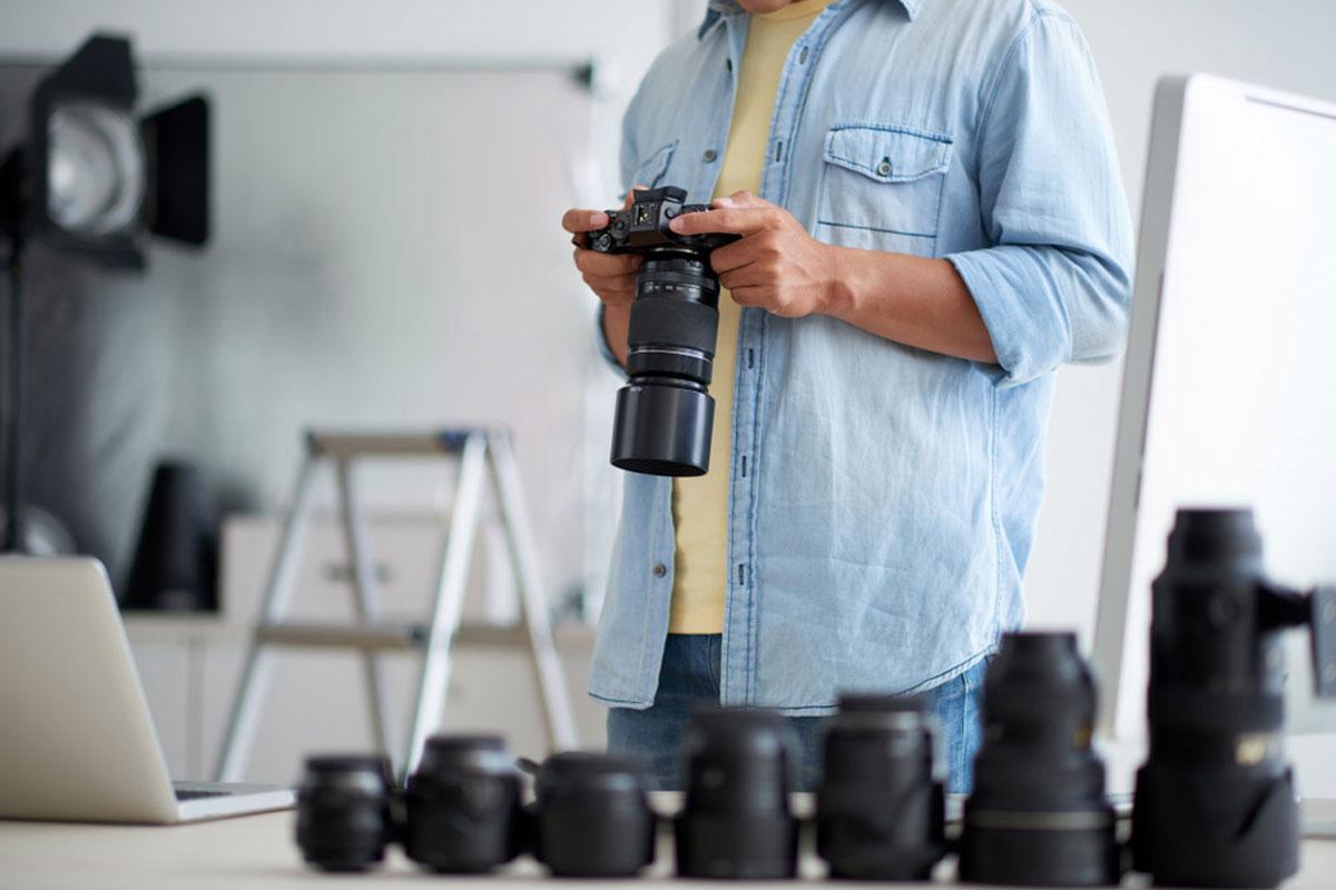 Lista de precios: Fotógrafo masculino con una amplia variedad de lentes de cámara profesionales